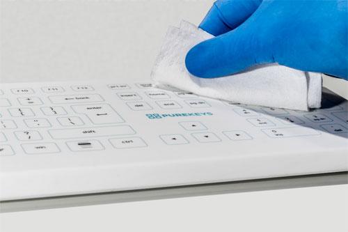 Reinigung des Hygienetastatur mit Handschuhen und einem Desinfaktionstuch.